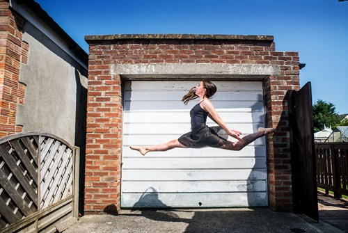Dancer leaping in front of garage